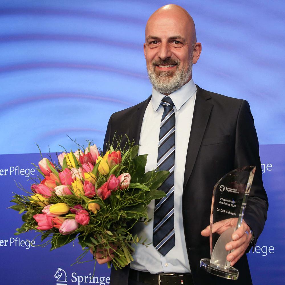 Dr. Dirk Ashauer, Pflegemanager 2020 mit Pokal und Blumen. Foto: Britta Pedersen